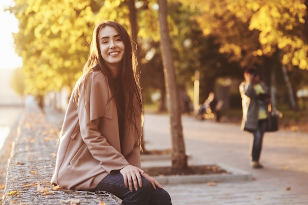 Young, pretty, smiling brunette girl sitting with hands on her knees, wearing casual coat with an autumn sunny park on the light blurry background.