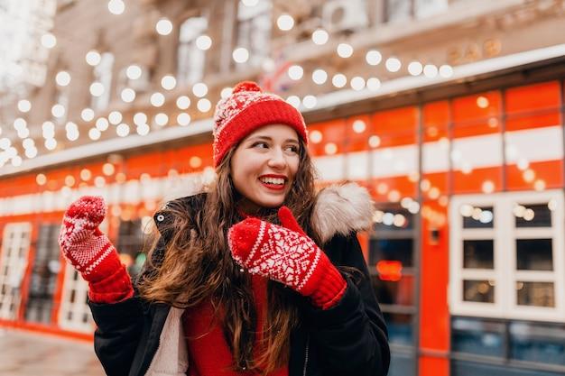 Молодая симпатичная улыбающаяся возбужденная счастливая женщина в красных рукавицах и вязаной шапке в зимнем пальто гуляет по городской улице, теплая одежда