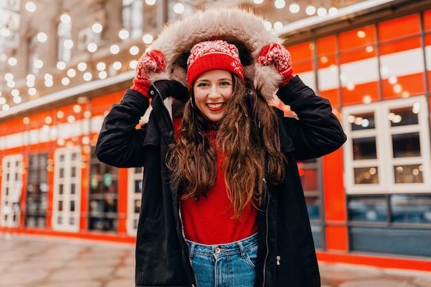 赤いミトンとニット帽を身に着けている若いかわいい笑顔の興奮した幸せな女性は、街の通りを歩いて、暖かい服を着て冬のコートを着ています