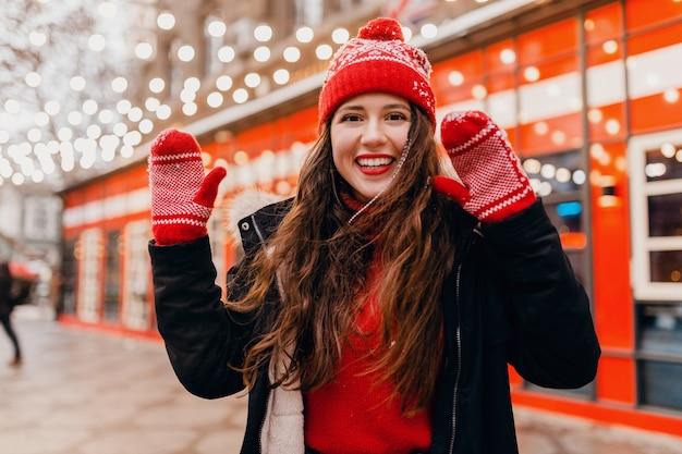 Giovane donna felice eccitata abbastanza sorridente in guanti rossi e cappello lavorato a maglia che indossa cappotto invernale che cammina nella strada di natale della città, tendenza di moda stile vestiti caldi
