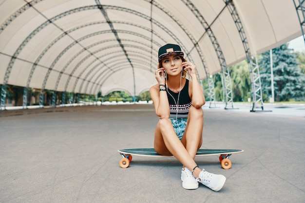 Young pretty smiling girl with a longboard