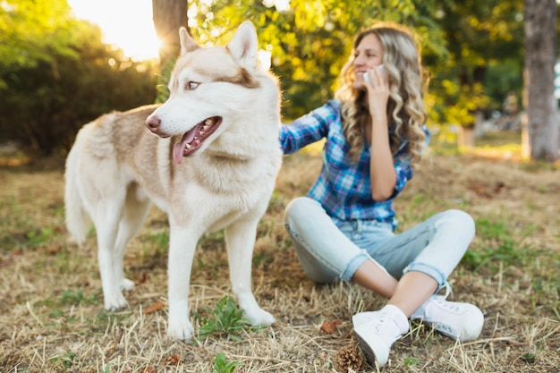 Young pretty smiling happy blond woman playing with dog husky breed in park on sunny summer day