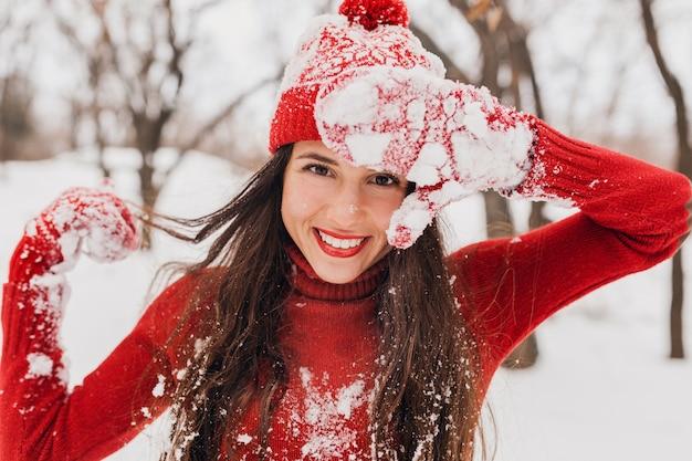 Молодая довольно улыбающаяся счастливая женщина в красных рукавицах и шляпе, носящая вязаный свитер, гуляет в парке в снегу, теплая одежда, веселится, машет длинными волосами