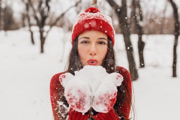 雪の中で公園を歩いて、暖かい服を着て、楽しんで、赤いミトンと帽子をかぶった若いかなり笑顔の幸せな女性