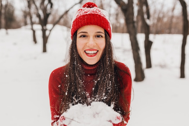 Молодая довольно улыбающаяся счастливая женщина в красных рукавицах и шляпе, носящая вязаный свитер, гуляет в парке в снегу, теплой одежде, веселится