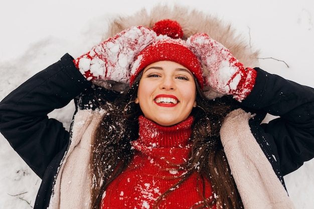 Молодая довольно улыбающаяся счастливая женщина в красных рукавицах и вязаной шапке в зимнем пальто, лежа в парке в снегу, теплой одежде, вид сверху