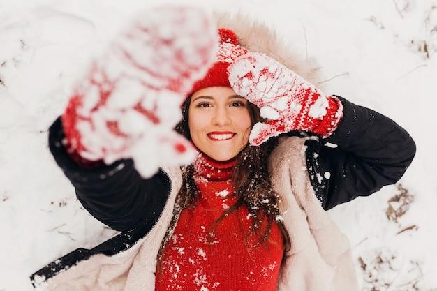 雪、暖かい服、上からの眺めの公園で横たわっている冬のコートを着て赤いミトンとニット帽の若いかなり笑顔の幸せな女性
