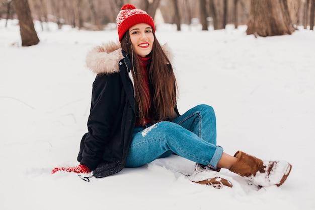 公園の雪の上に座って冬のコート、暖かい服を着て赤いミトンとニット帽の若いかなり笑顔の幸せな女性