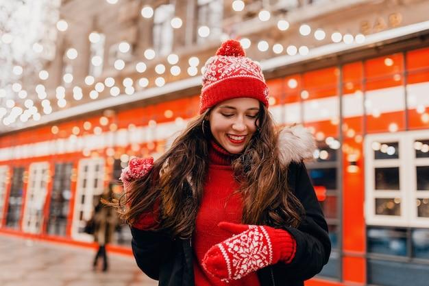 Молодая довольно улыбающаяся счастливая женщина в красных рукавицах и вязаной шапке в зимнем пальто гуляет по городской рождественской улице, модная тенденция в стиле теплой одежды