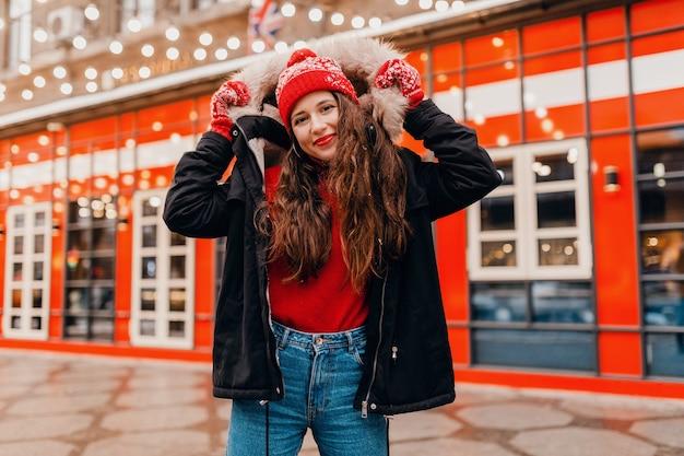 赤いミトンとニット帽を身に着けている若いかわいい笑顔の幸せな女性は、街の通りを歩いて、暖かい服を着て冬のコートを着ています