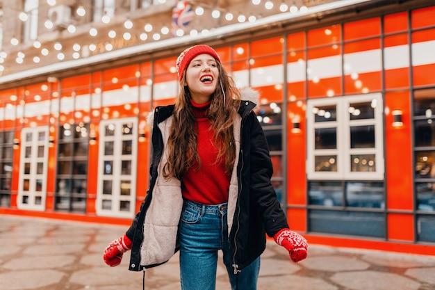 Молодая красивая улыбающаяся счастливая женщина в красных рукавицах и вязаной шапке в зимнем пальто гуляет по городской улице, теплая одежда