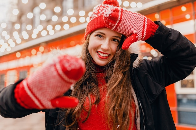 빨간 장갑과 도시 거리, 따뜻한 옷을 걷고 겨울 코트를 입고 니트 모자에 젊은 꽤 웃는 행복 한 여자