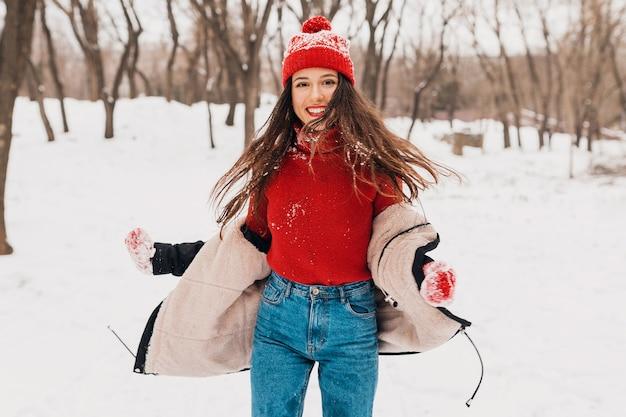 雪の中で公園を歩いて、暖かい服を着て、楽しんで、赤いミトンと冬のコートを着たニット帽の若いかわいい笑顔の幸せな女性