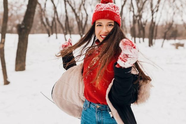 Молодая красивая улыбающаяся счастливая женщина в красных рукавицах и вязаной шапке в зимнем пальто гуляет в парке в снегу, теплой одежде, веселится