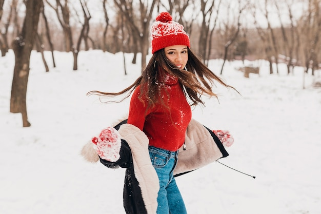 赤いミトンと冬のコートを着て、雪の中で公園を歩いて、暖かい服を着たニット帽の若いかわいい笑顔の幸せな女性