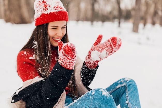 Молодая довольно улыбающаяся счастливая женщина в красных рукавицах и вязаной шапке в зимнем пальто, гуляет в парке, играет со снегом в теплой одежде