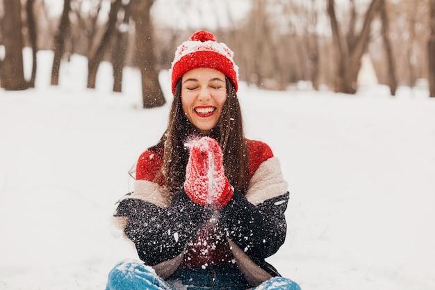 赤いミトンとニット帽を着て、冬のコートを着て、公園を歩いて、暖かい服を着て雪で遊んで、若いかわいい笑顔の幸せな女性