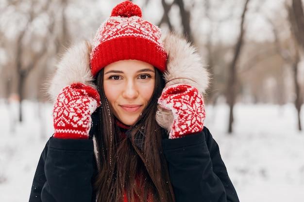 Молодая красивая улыбающаяся счастливая женщина в красных рукавицах и вязаной шапке в зимнем пальто с меховым капюшоном, гуляет в парке в снегу, теплой одежде