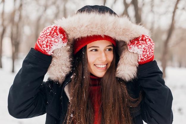 赤いミトンと毛皮のフード付きの冬のコートを着て、雪の中で公園を歩いて、暖かい服を着たニット帽の若いかわいい笑顔の幸せな女性