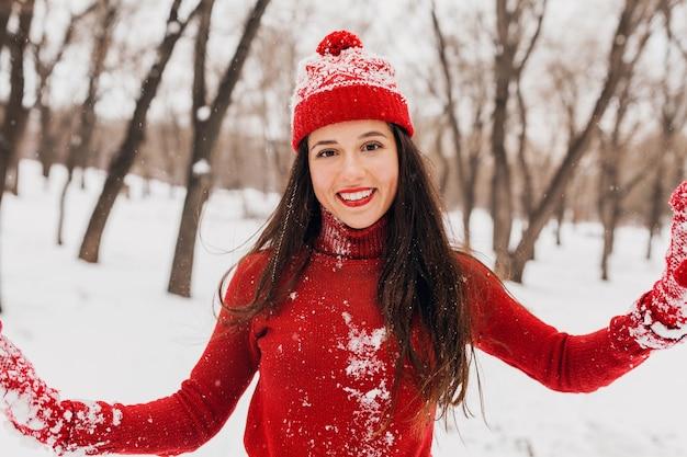 Giovane bella donna felice sorridente in guanti rossi e cappello che indossa un maglione lavorato a maglia a piedi nel parco nella neve, vestiti caldi, divertirsi, agitando i capelli lunghi