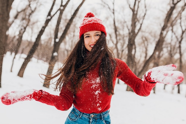 Young pretty smiling happy woman in red mittens and hat wearing knitted sweater walking in park in snow, warm clothes, having fun, waving long hair