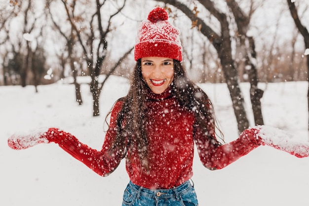 Giovane donna felice abbastanza sorridente in guanti rossi e cappello che indossa un maglione lavorato a maglia a piedi nel parco nella neve, vestiti caldi, divertendosi