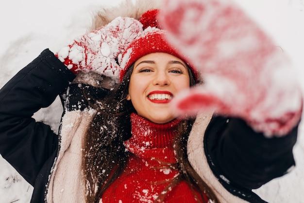 Giovane bella donna felice sorridente in guanti rossi e berretto lavorato a maglia che indossa cappotto invernale giacente nel parco nella neve, vestiti caldi, vista da sopra
