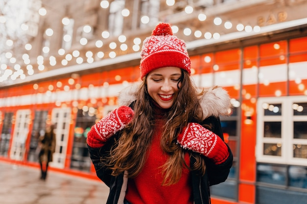 Young pretty smiling happy woman in red mittens and knitted hat wearing winter coat walking in city christmas street, warm clothes style fashion trend