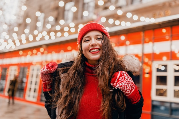 Young pretty smiling happy woman in red mittens and knitted hat wearing winter coat walking in city street, warm clothes