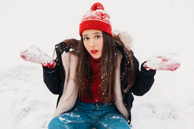 Giovane bella donna felice sorridente in guanti rossi e cappello lavorato a maglia che indossa cappotto invernale, passeggiate nel parco, giocando con la neve in vestiti caldi