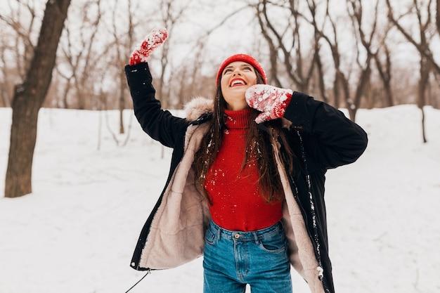 Giovane bella donna felice sorridente in guanti rossi e cappello lavorato a maglia che indossa cappotto invernale passeggiate nel parco nella neve, vestiti caldi, divertendosi