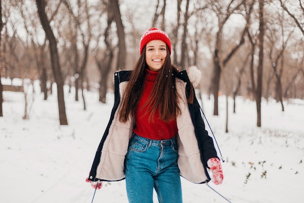 Young pretty smiling happy woman in red mittens and knitted hat wearing winter coat, walking in park in snow, warm clothes