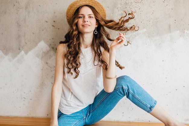 Молодая довольно улыбающаяся счастливая женщина в синих джинсах и белой рубашке