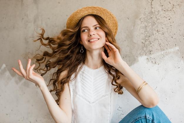 Молодая довольно улыбающаяся счастливая женщина в белой рубашке сидит у стены в соломенной шляпе