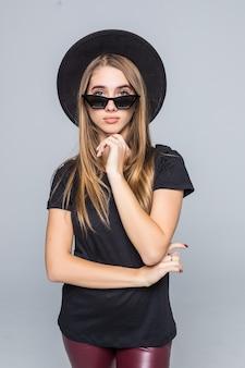 黒い帽子、黒いtシャツ、暗いズボンをあごの下の灰色の背景の拳で分離された服を着て華麗なサングラスの若いかなり笑顔の女性