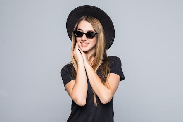 黒い帽子、黒いtシャツ、灰色の背景に分離された暗いズボンで着飾った鮮やかなサングラスの若いかなり笑顔の女性が一緒にあごの下で手を握る