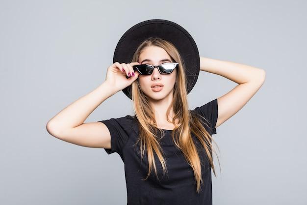 黒の帽子、黒のtシャツ、灰色の背景に分離された暗いズボンで着飾った鮮やかなサングラスの若いかなり笑顔の女性