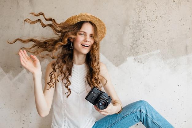 Молодая симпатичная стильная женщина в синих джинсах и белой рубашке у стены в соломенной шляпе