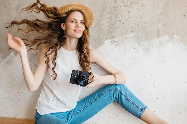 밀짚 모자에 벽에 블루 데님 청바지와 흰색 셔츠를 입고 젊은 꽤 웃는 세련된 여자