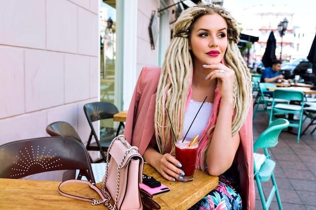 屋外の街のかわいいカフェでポーズをとる若いかわいい笑顔の女性、エレガントでスタイリッシュな服、珍しいブロンドの恐怖の髪型。ポジティブな感情、ファッションの詳細。夏の街の旅。