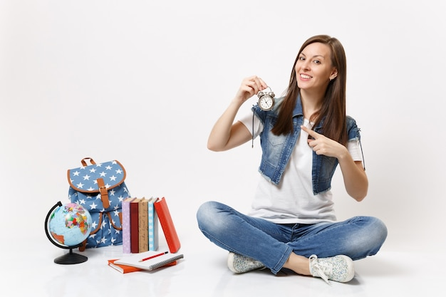 Young pretty smiling woman student pointing index finger on alarm clock sitting near globe, backpack, school books isolated