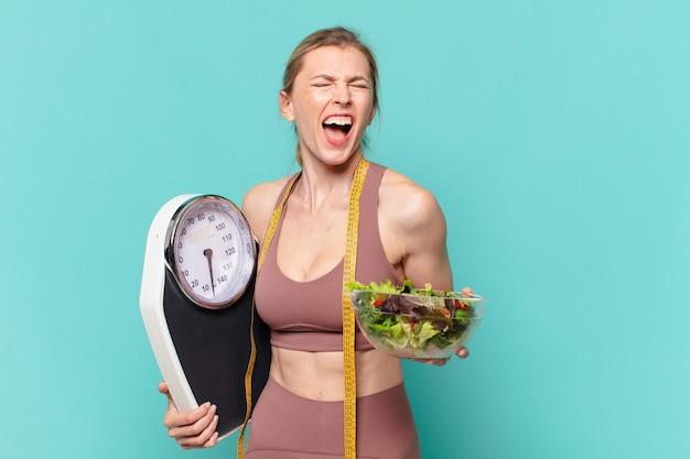 Молодая красивая спортивная женщина сердитое выражение и держит весы и салат