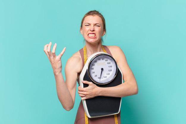 Молодая красивая спортивная женщина сердитое выражение и держит весы