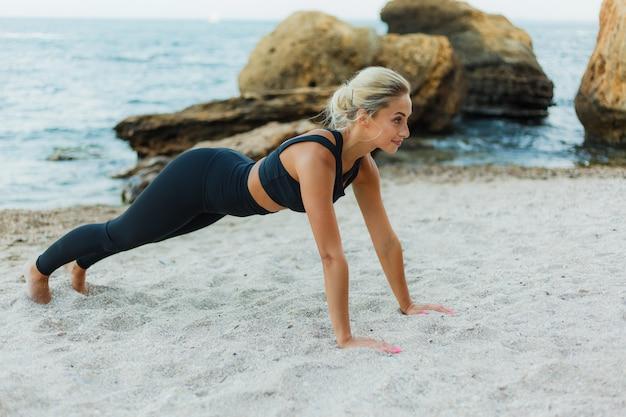 Young pretty sport woman blonde in sportswear does pushups from sand on wild beach. outdoor training