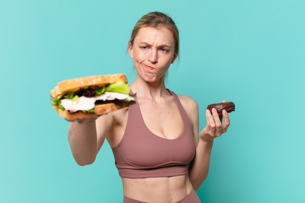 Молодая симпатичная спортивная женщина с сомнением или неуверенным выражением лица держит бутерброд и пончик