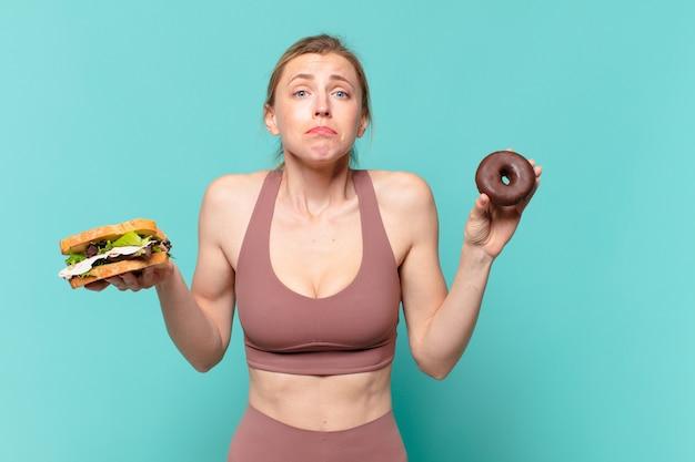 Молодая красивая спортивная женщина, сомневающаяся или неуверенное выражение и держащая бутерброд и пончик