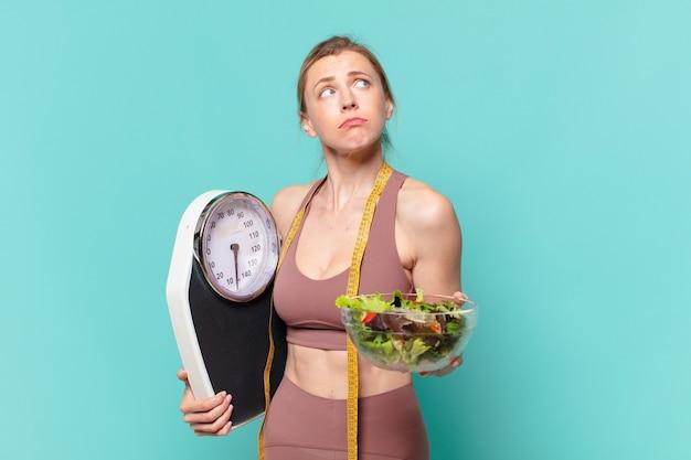 Молодая красивая спортивная женщина, сомневающаяся или неуверенное выражение и держащая весы и салат