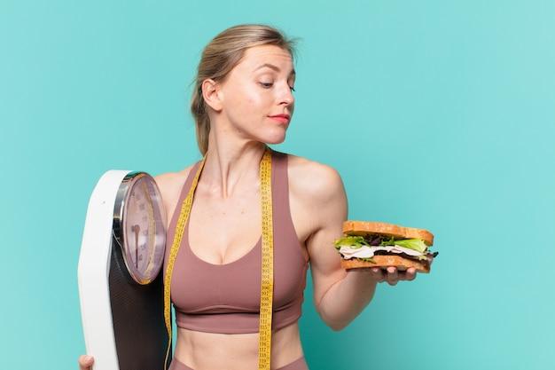 Молодая красивая спортивная женщина, сомневающаяся или неуверенное выражение и держащая весы и бутерброд