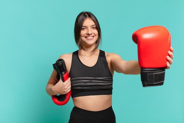 若いかわいいスポーツ女性の幸せな表情とボクシンググローブ