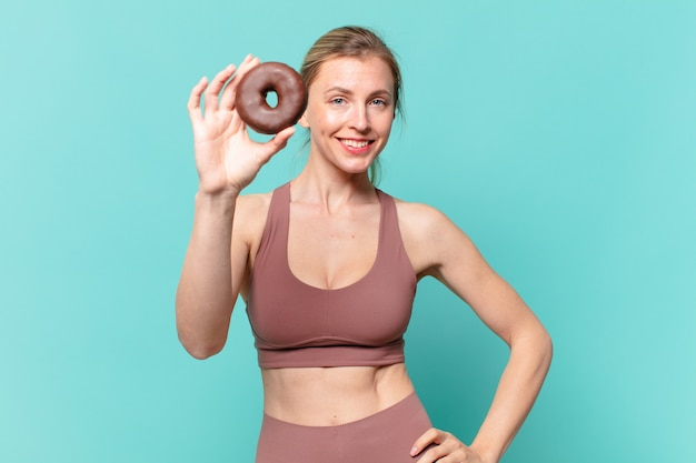 若いかわいいスポーツの女性の幸せな表現とドーナツを保持しています